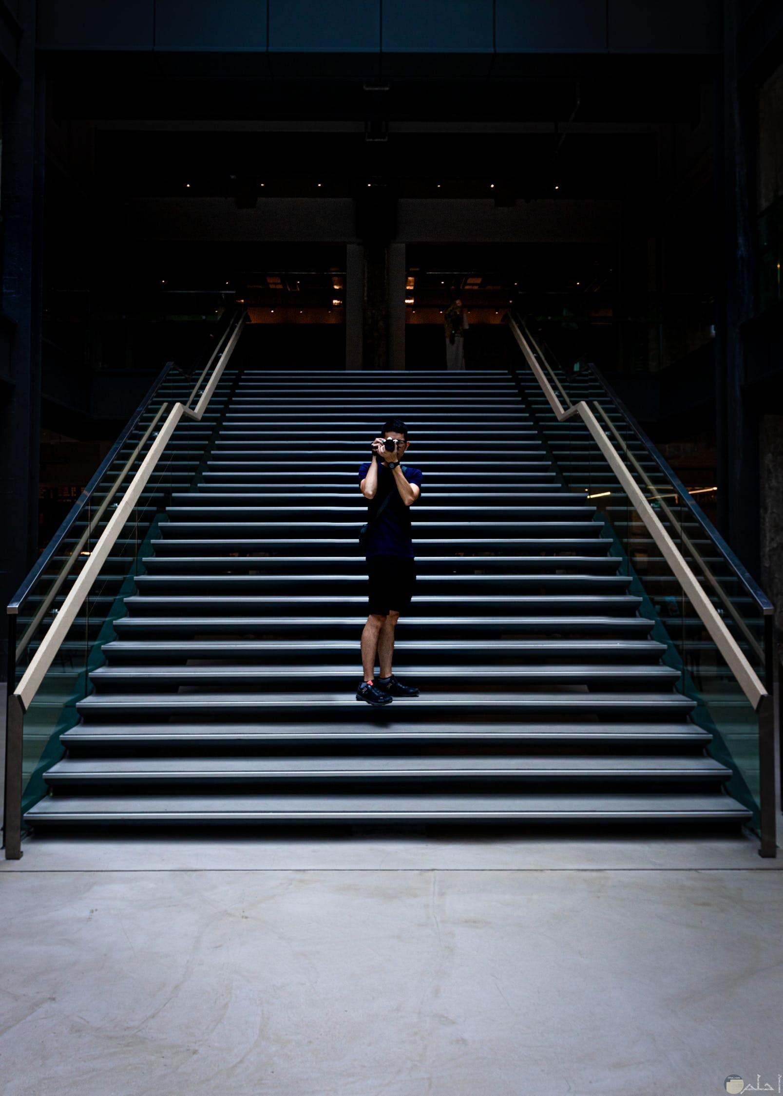 صوره فتاه تقف علي سلم ترتدي طقم اسود وبيدها كاميرا تصوير تقوم بالتصوير بها