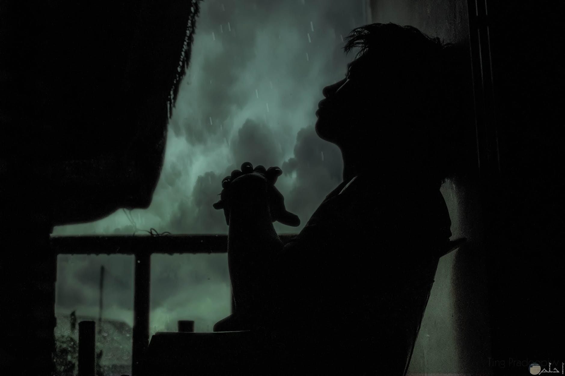 صورة شخص جالس يفكر في الظلام بمفرده
