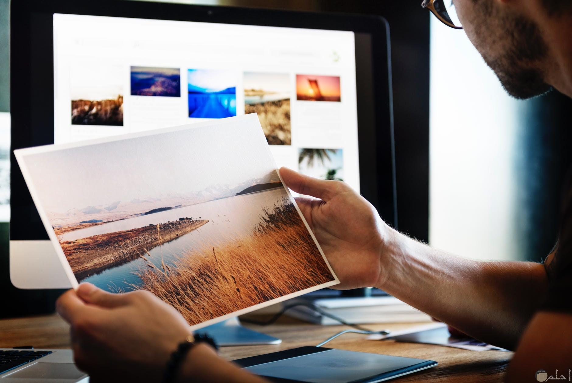صوره شخص يفتح صور علي جوجل وقام بطبعها وبيده صوره مطبوعه