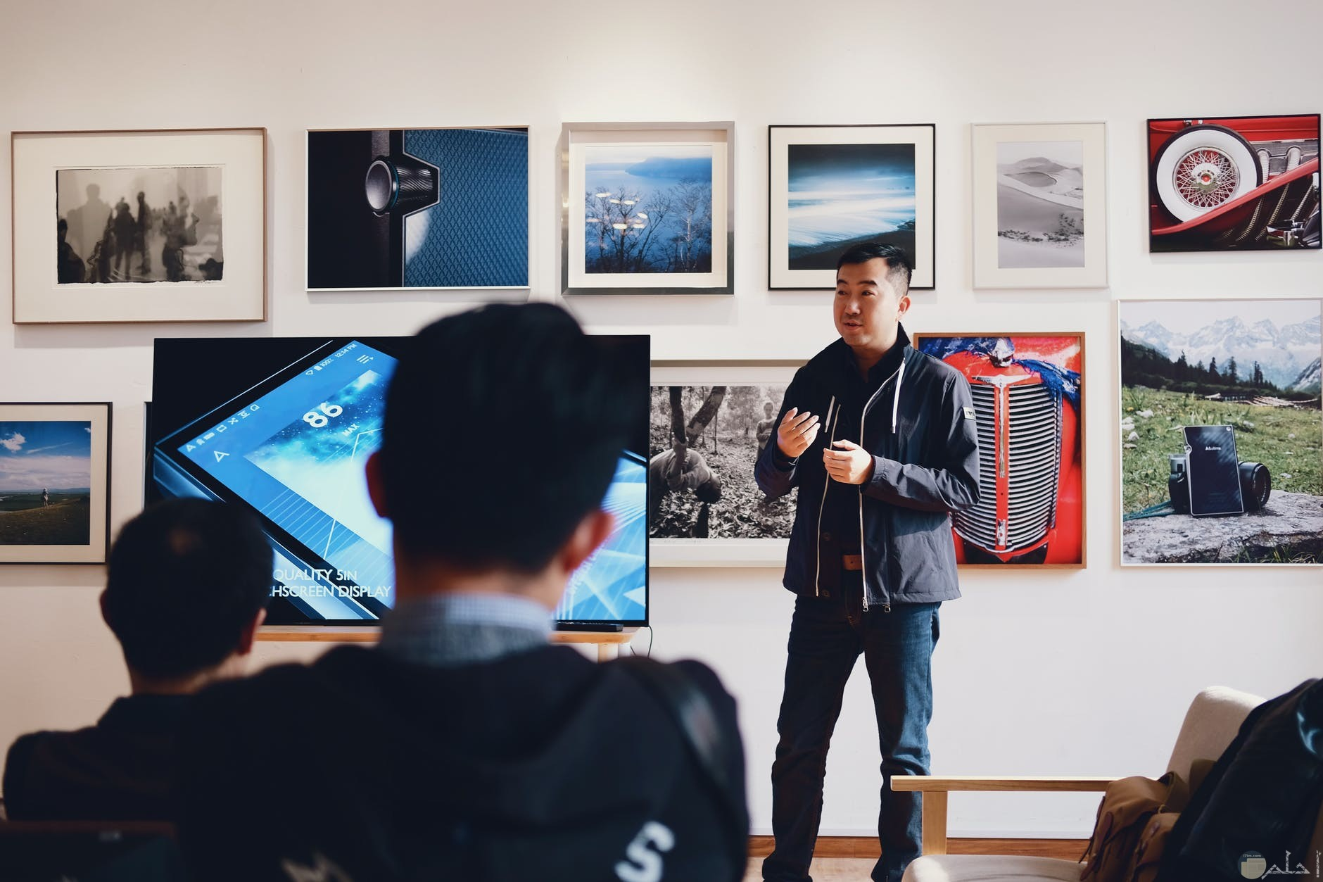 رجل ياباني يشرح للشباب في حجره بها جهاز ناقل للمعلومات والعديد من الصور علي الحائط