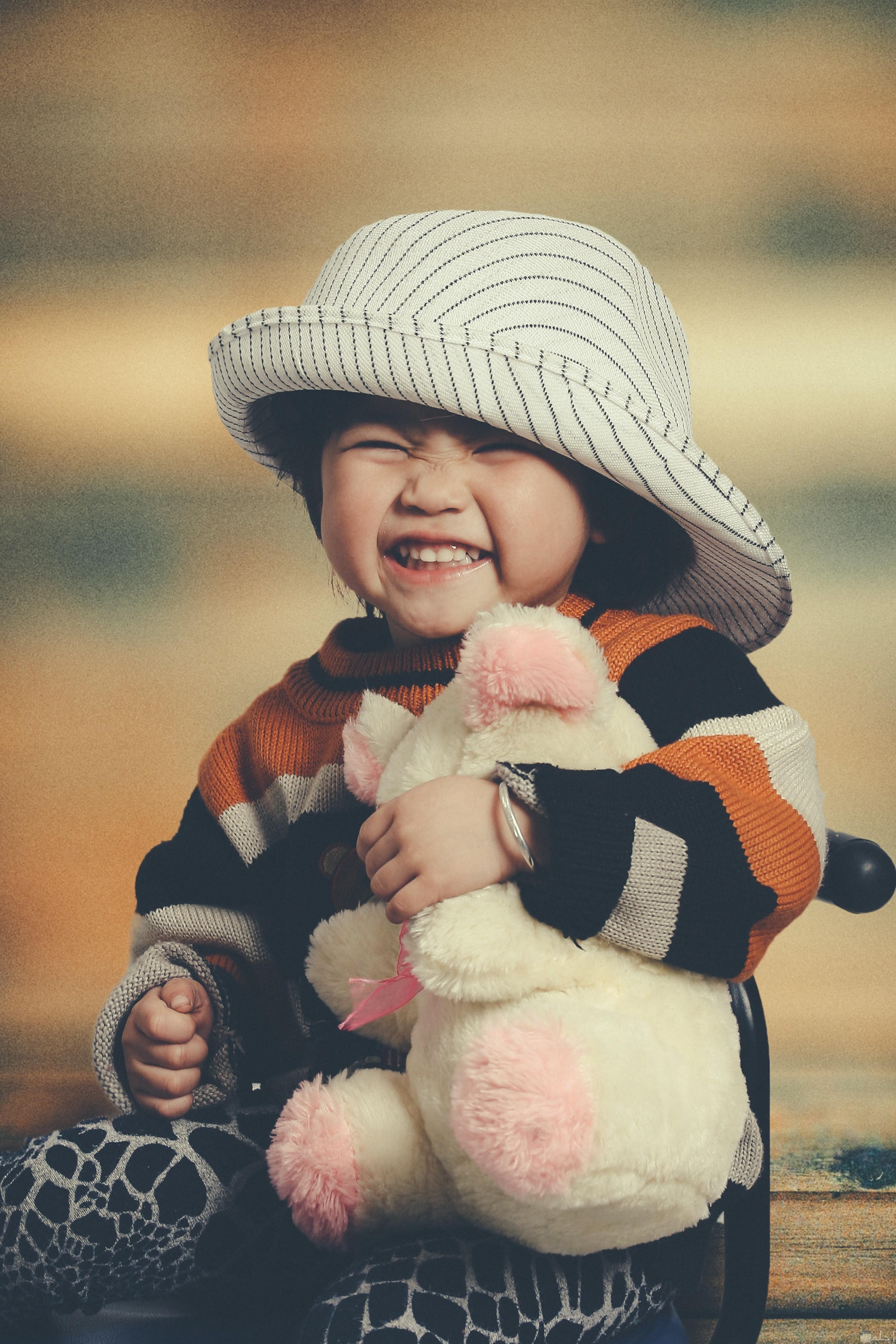 صورة طفل يمسك دبدوب