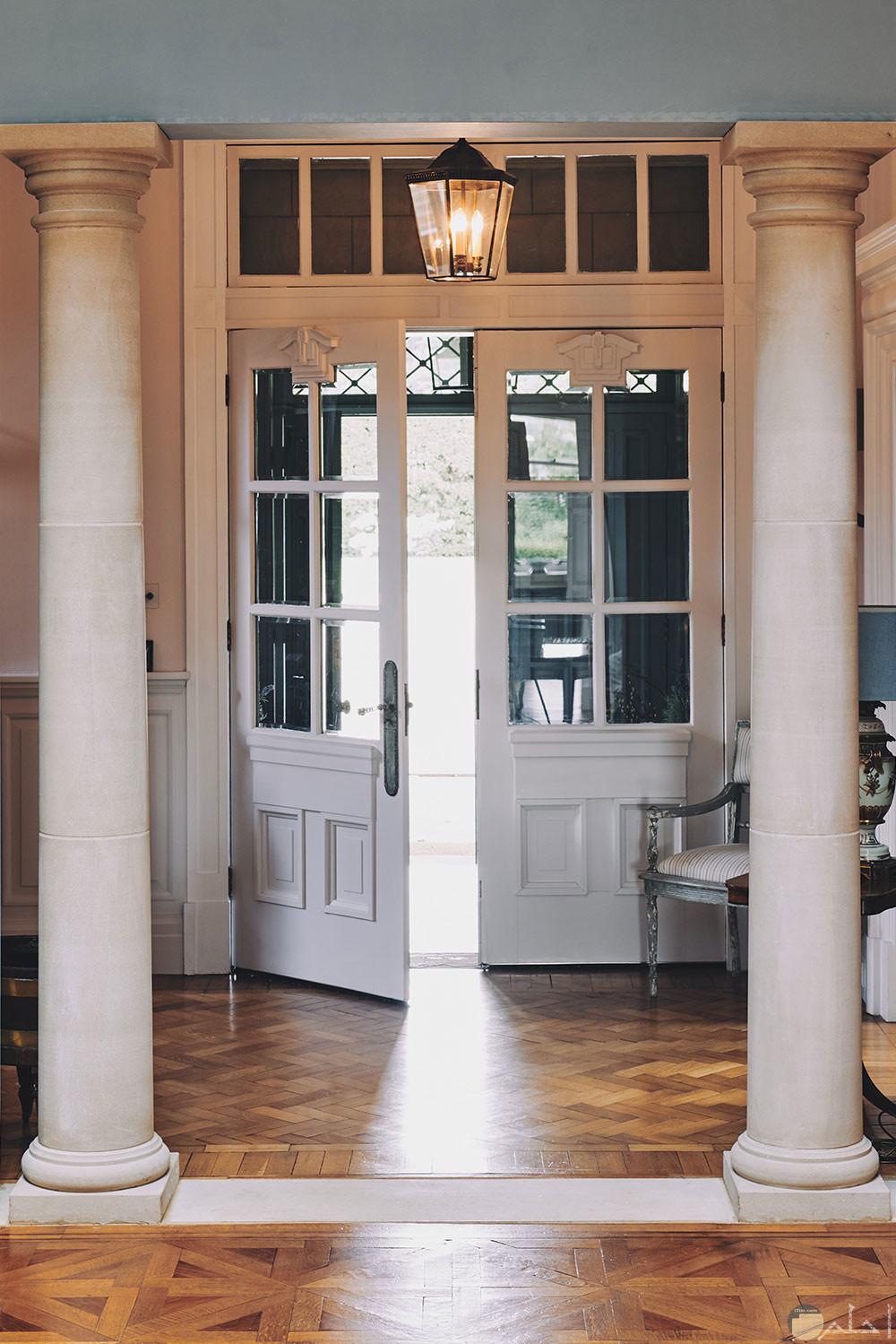 باب منزل داخلى كبير الحجم لونة ابيض وبه مربعات زجاج