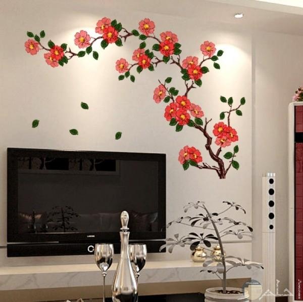 حائط بيضاء وعليها رسمه غصن به العديد من الورود الحمراء