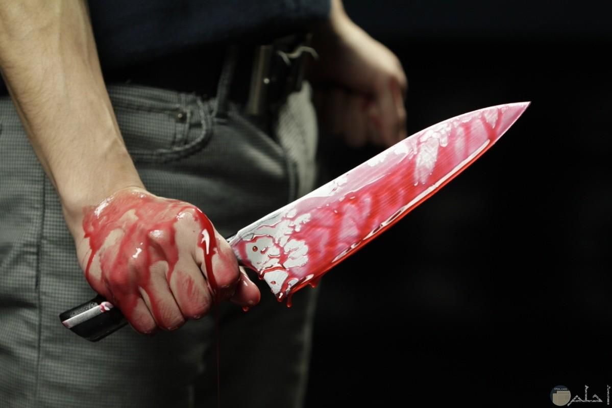 شخص يحمل سكين عليه دماء