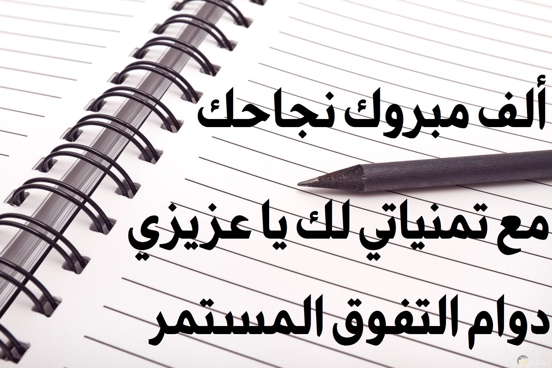 صورة تهنئة بمناسبة النجاح مكتوب عليها كلمات تهنئة علي دفتر مع قلم فوقه
