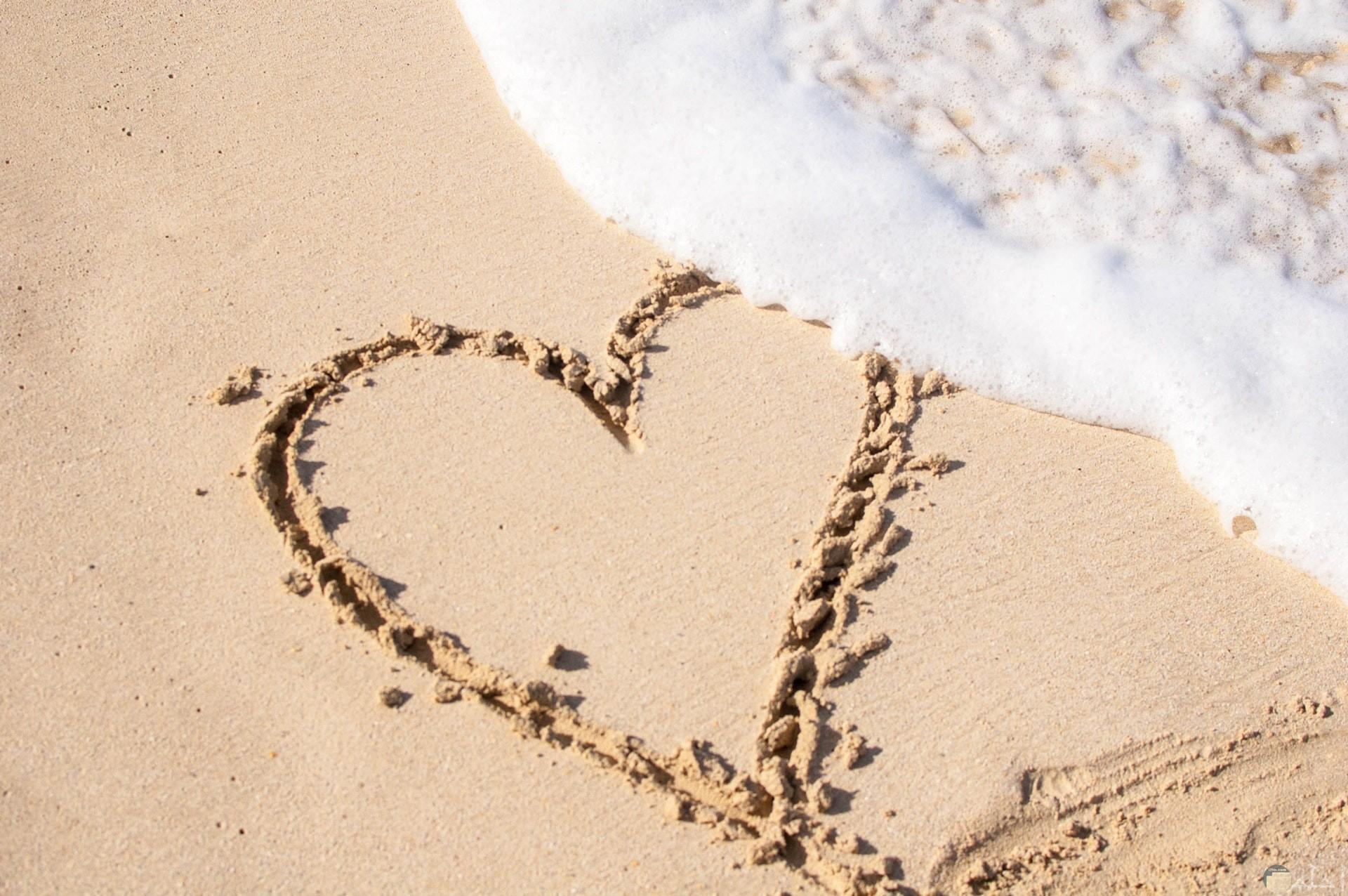 صورة جميلة جدا لقلب مرسوم علي رمال الشاطئ بجانبه مياة البحر