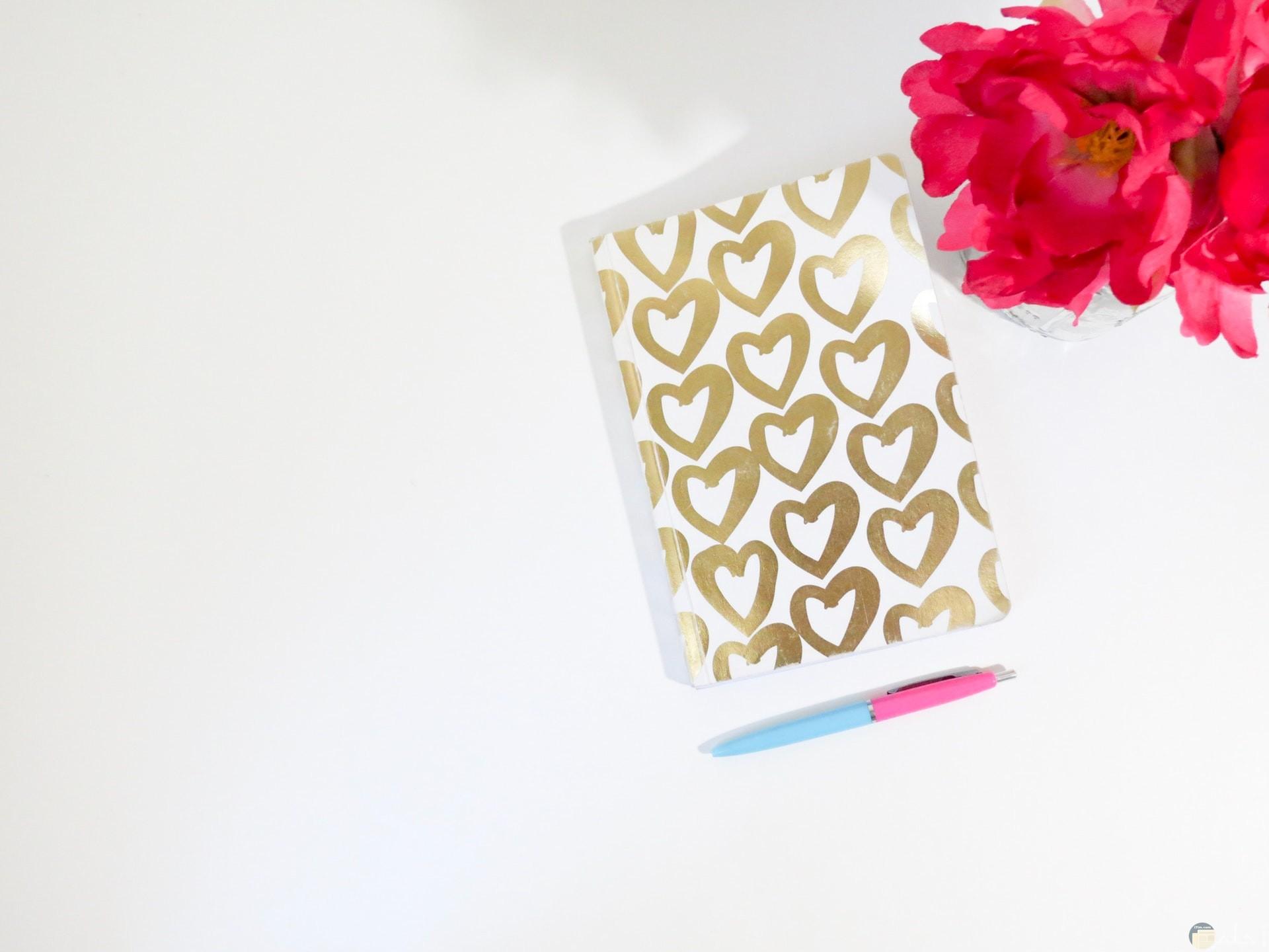 صورة جميلة جدا لقلوب حلوة موجودة علي غلاف دفتر بجانب باقة ورد وقلم