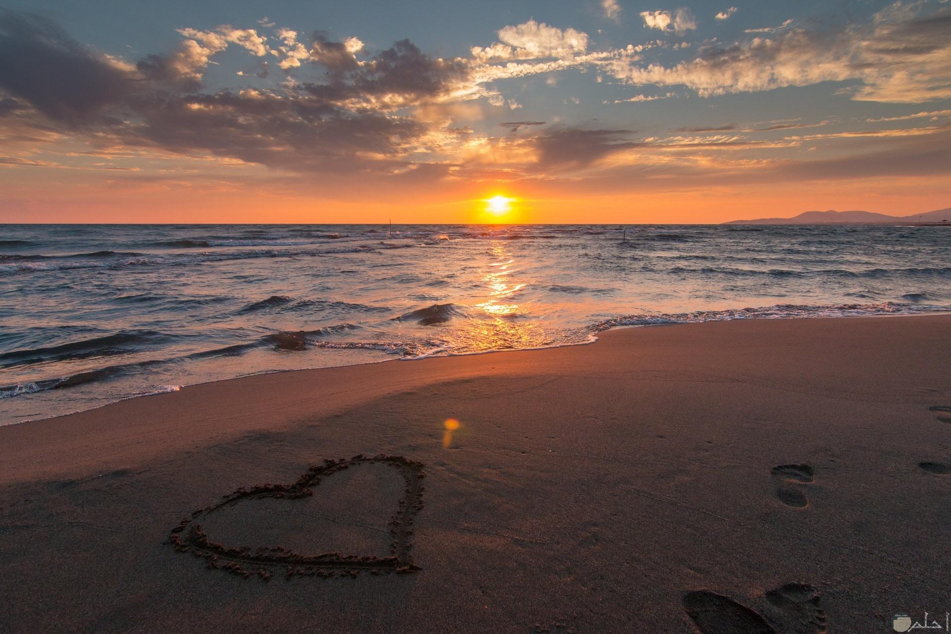 صورة جميلة لقلب مرسوم علي رمال الشاطئ بجانب البحر وقت الغروب