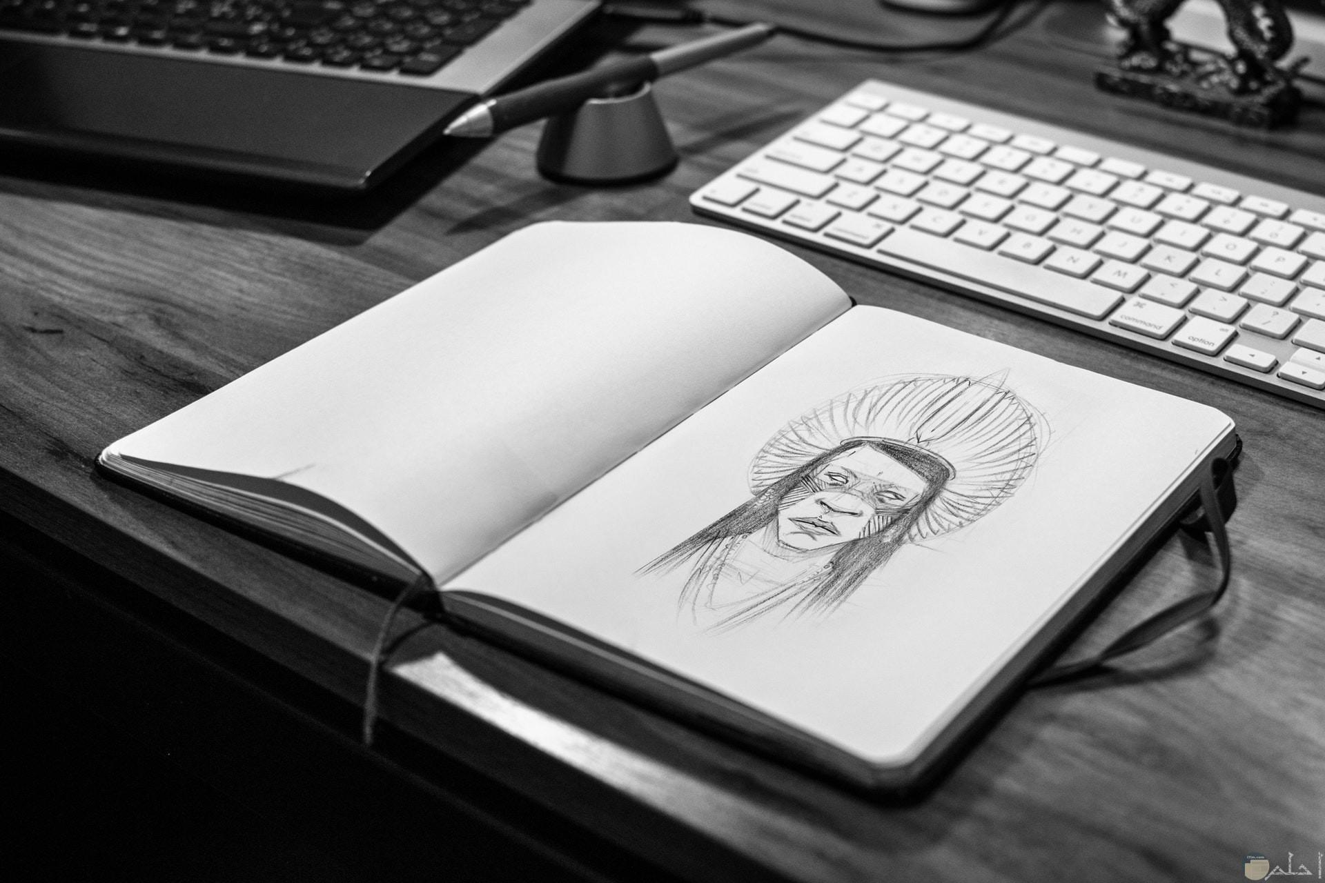 صورة لرسمة رجل من الهنود الحمر علي دفتر بجانبه لوحة مفاتيح كمبيوتر وقلم