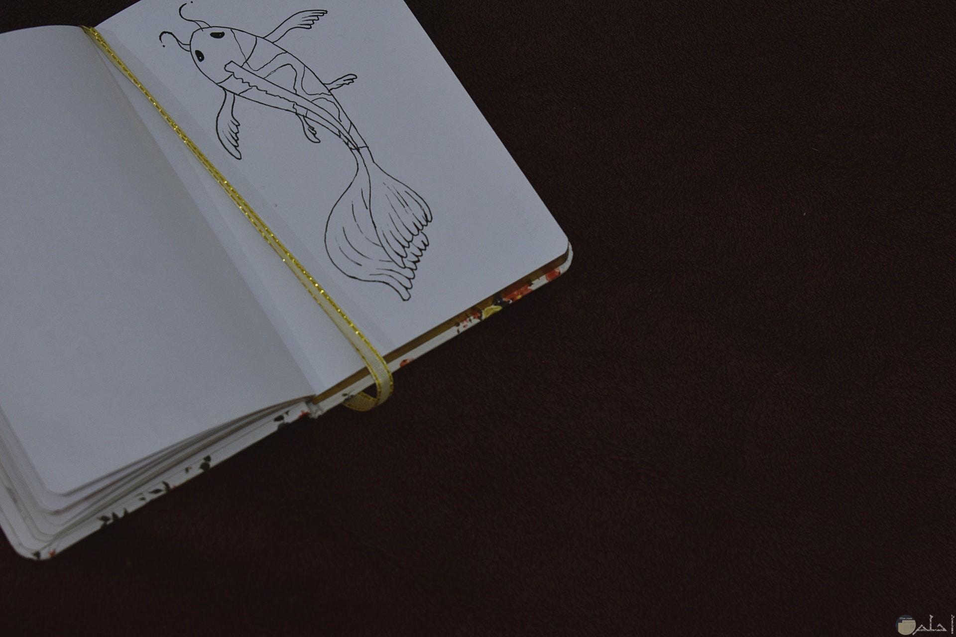 صورة لرسمة سمكة غريبة في دفتر
