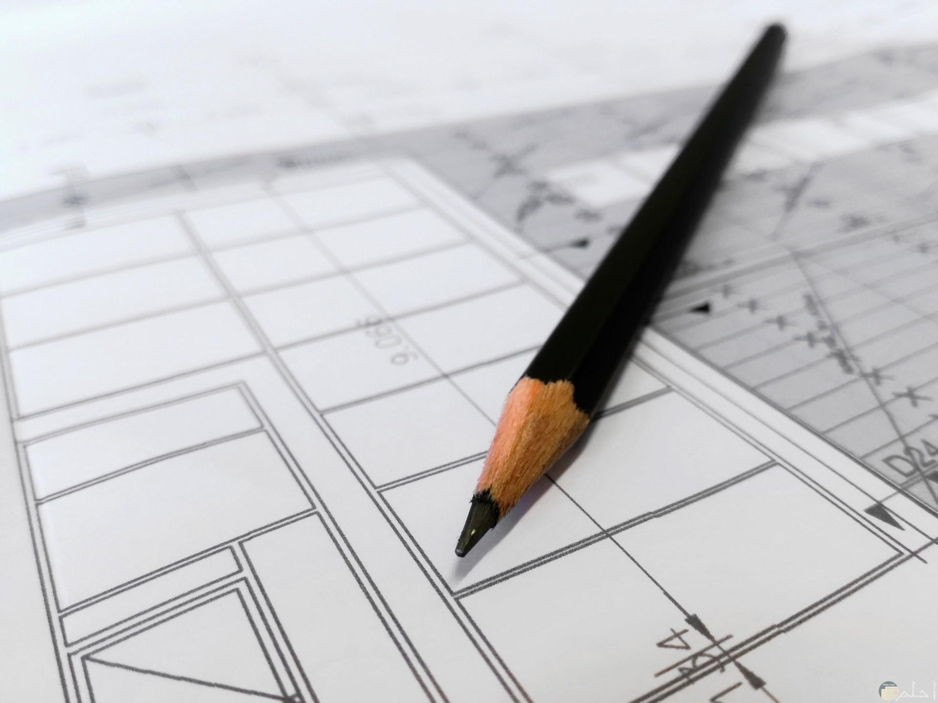 صورة لرسمة هندسية علي الورق فوقها قلم رصاص