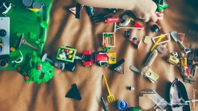 صورة مميزة جدا لمجموعة من الألعاب المختلفة للأطفال وطفل صغير يلعب بلعبة منهم