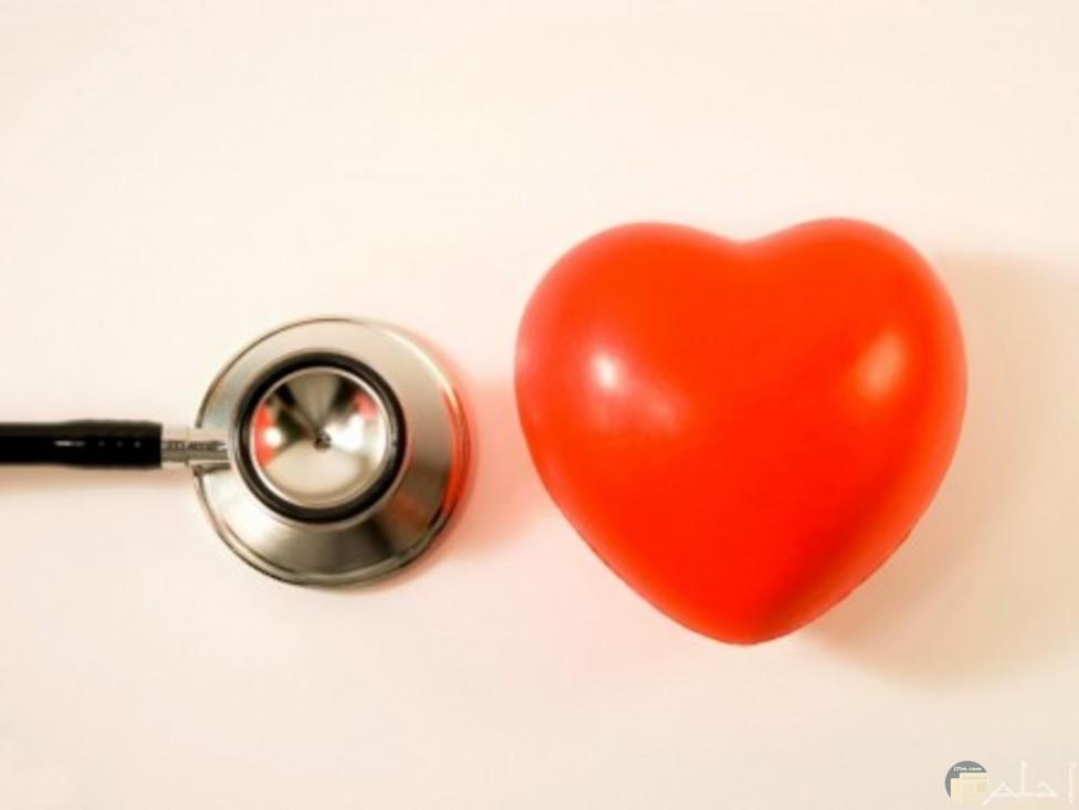 سماعه طبيب للقلب وبجوارها قلب احمر ولهان