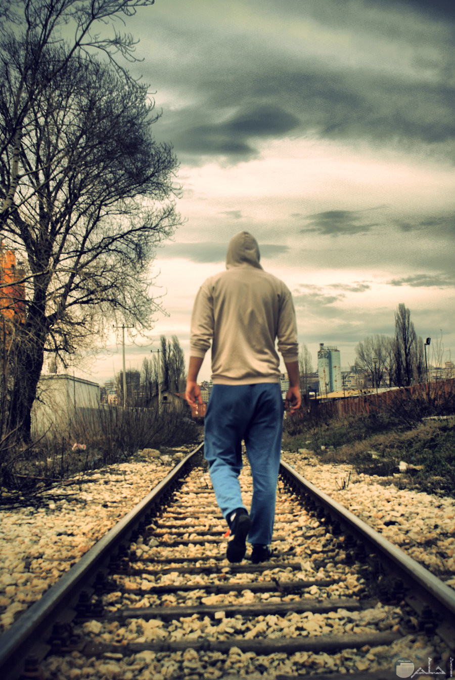 شاب يمشي على شريط قطار