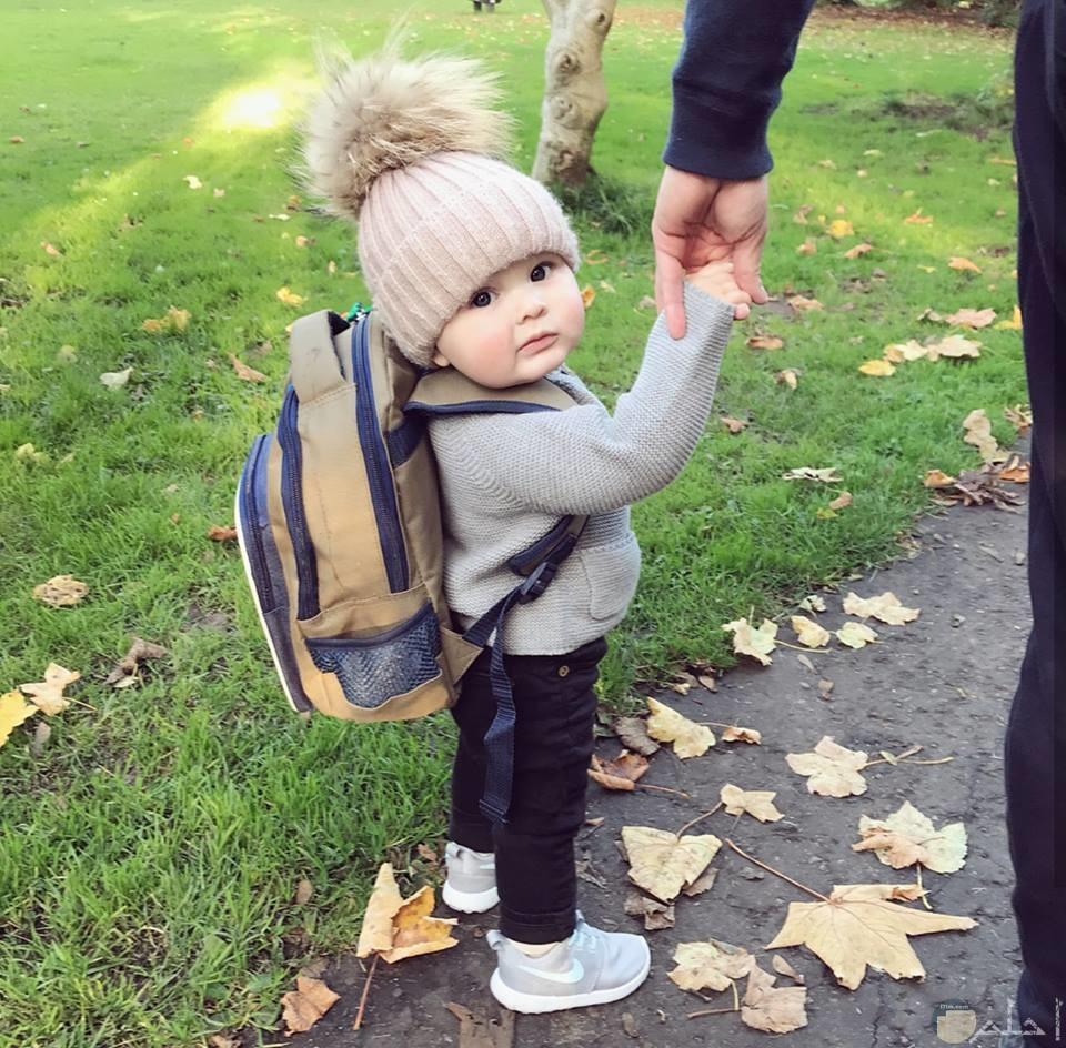 بيبي جميل يحمل حقيبة ويمسك بيد والده