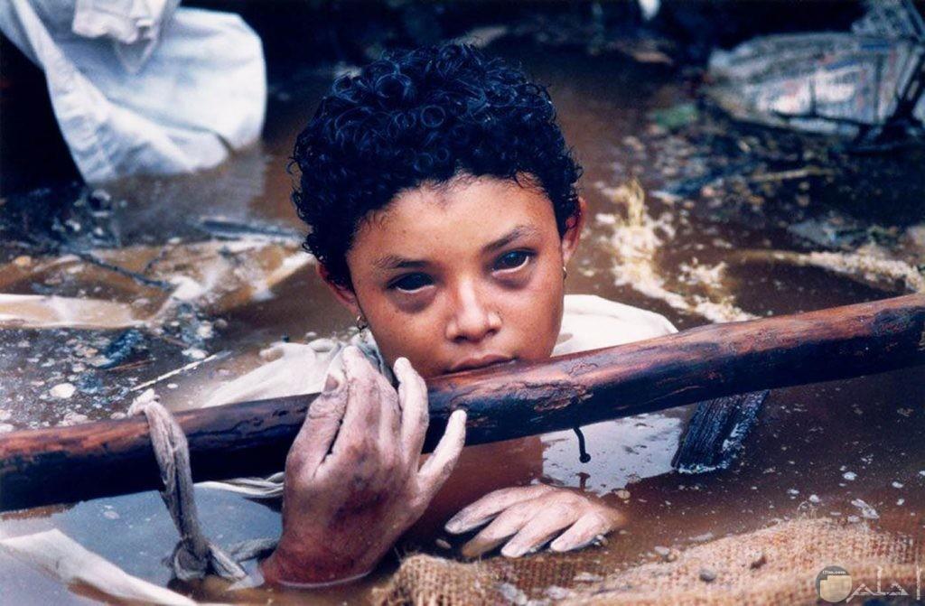 صورة مرعبة جدا لطفل يخرج نصفة من بركة ماء ملوثة وينظر بطريقة مخيفة