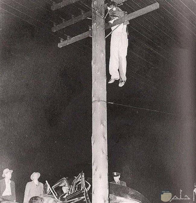 صورة لشاب مشنوق فوق عمود كهرباء وسط الاسلاك