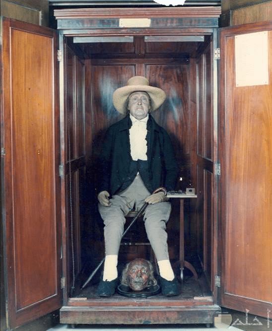 صورة مرعبة لرجل جالس داخل دولاب وبين قدمة طبق به راس انسان اخر
