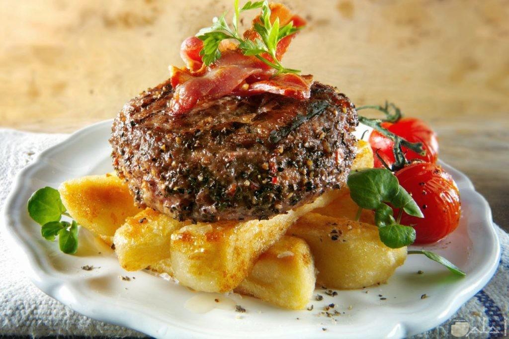 طبق به قطعه لحم وتحته بطاطس شرائح محمره واللجم مشوي فوقه لانشون وبجانبه ثمرتين طماطم