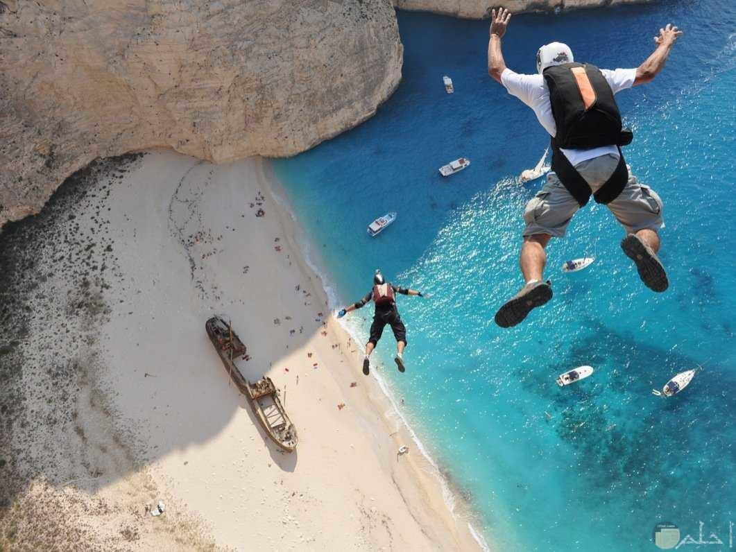 رجلين يقفزا من اعالى على شاطئ البحر