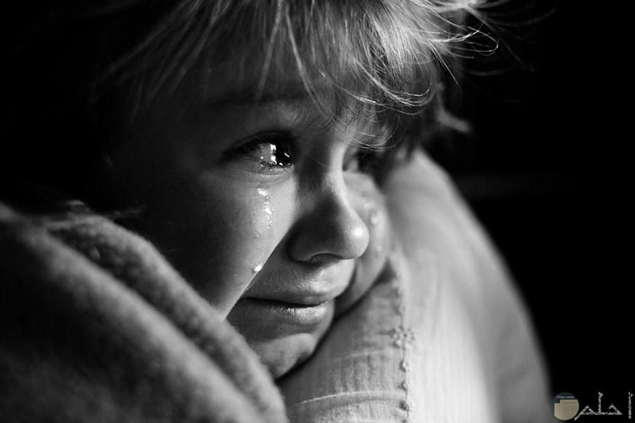 ولد صغير يبكى وتظهر على ملامح وجهه الخوف