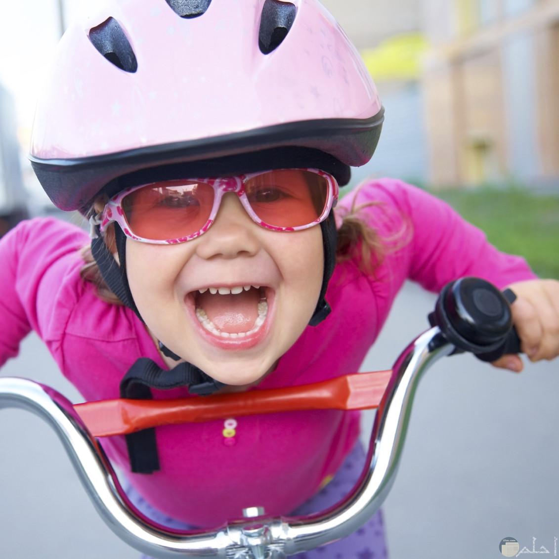 تعبير وجه بنوتة صغيرة سعيدة وهي تقود دراجة