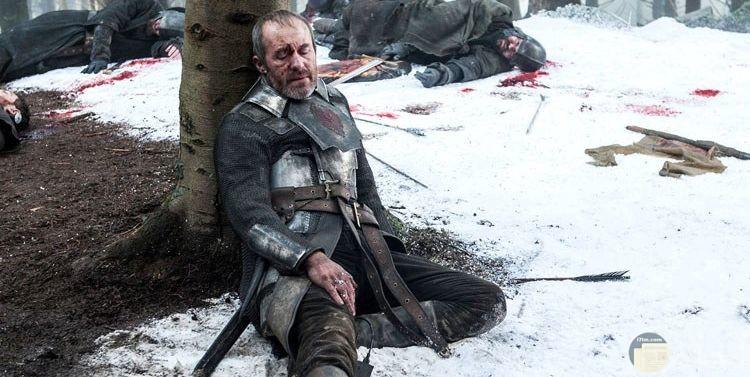 صورة اكشن لرجل مصاب يستريح بجوار شجرة وحوله اشخاص مقتوليين ودماء