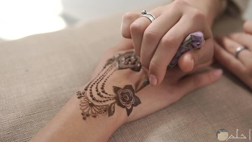 صورة بها يد فتاه ترسم الحنه على يد فتاه اخرى