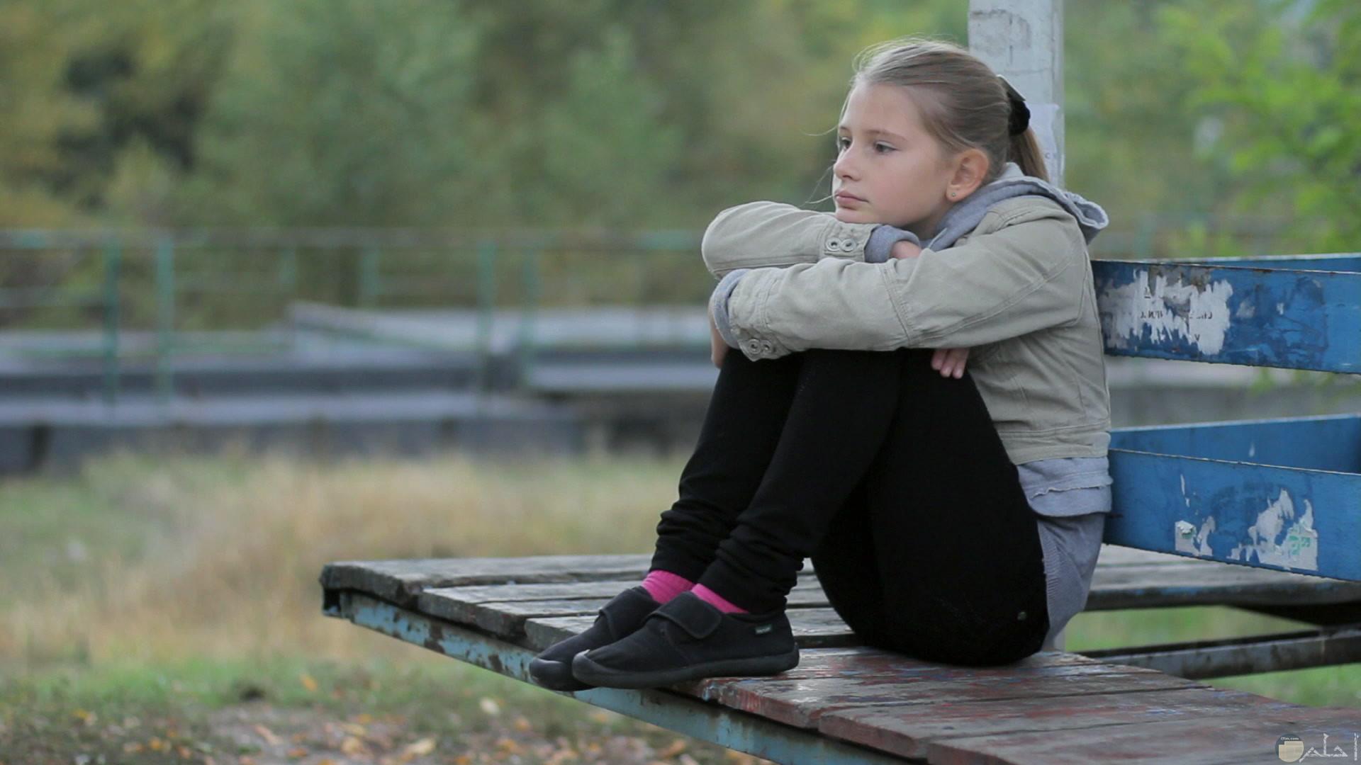 فتاة جالسة بمفردها مربعة يدها زعلانه جدا