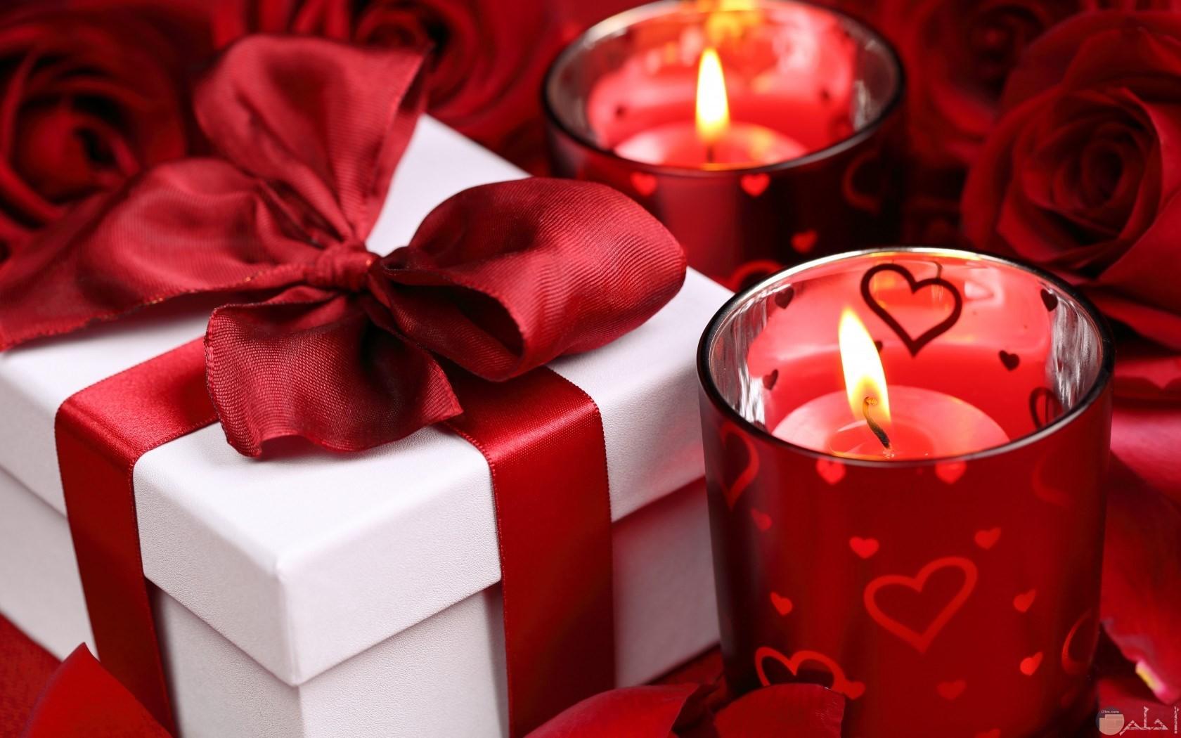 كاسات شمع احمر وهديه محاطه بورود حمراء تناسب مناسبات سعيدة مختلفة