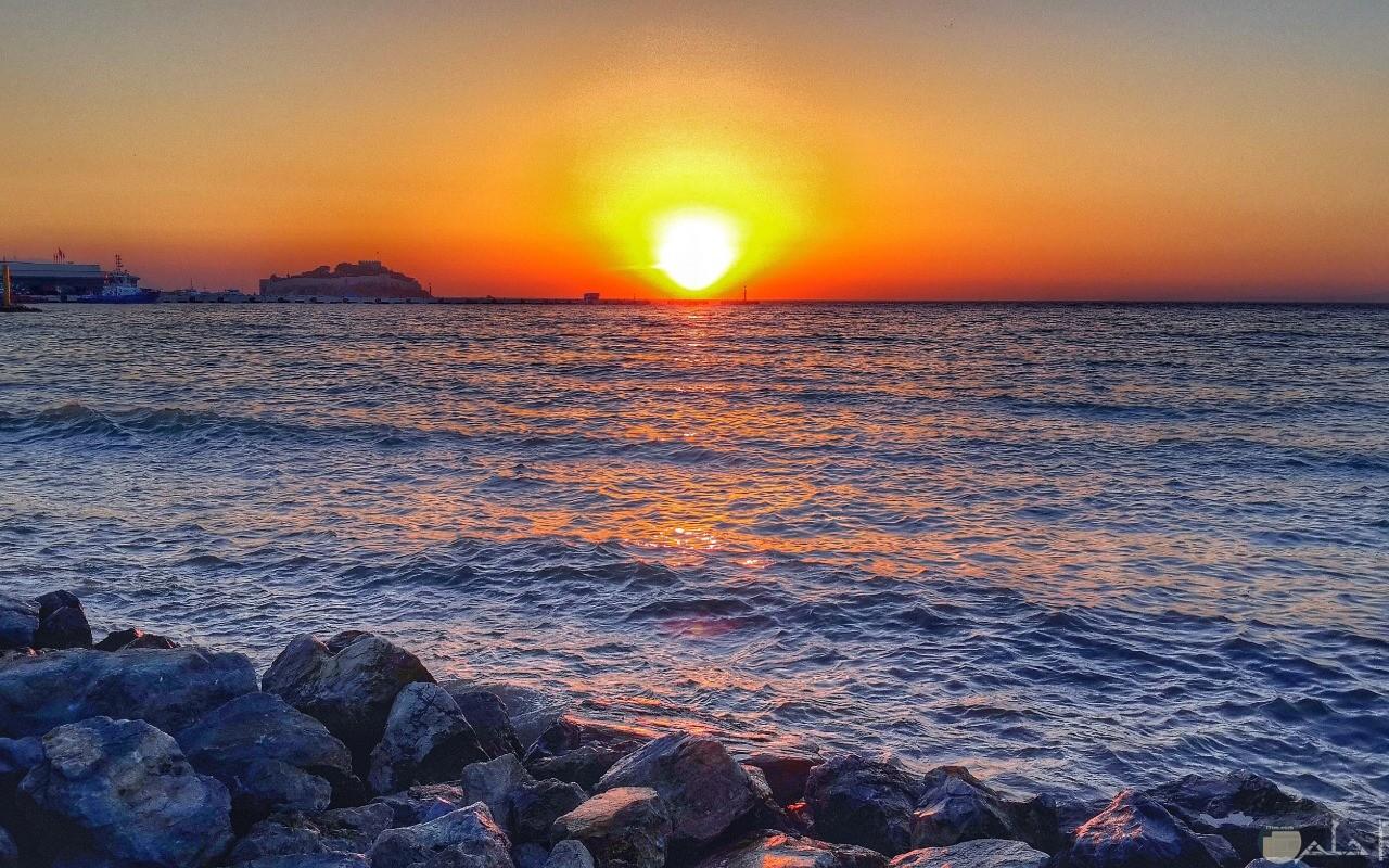 غروب الشمس عل البحر و الصخور.