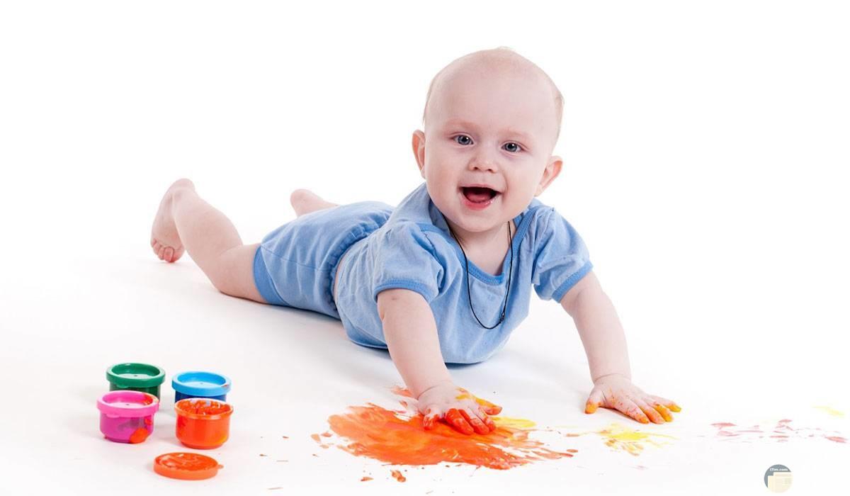 طفل صغير يلعب بالألوان.