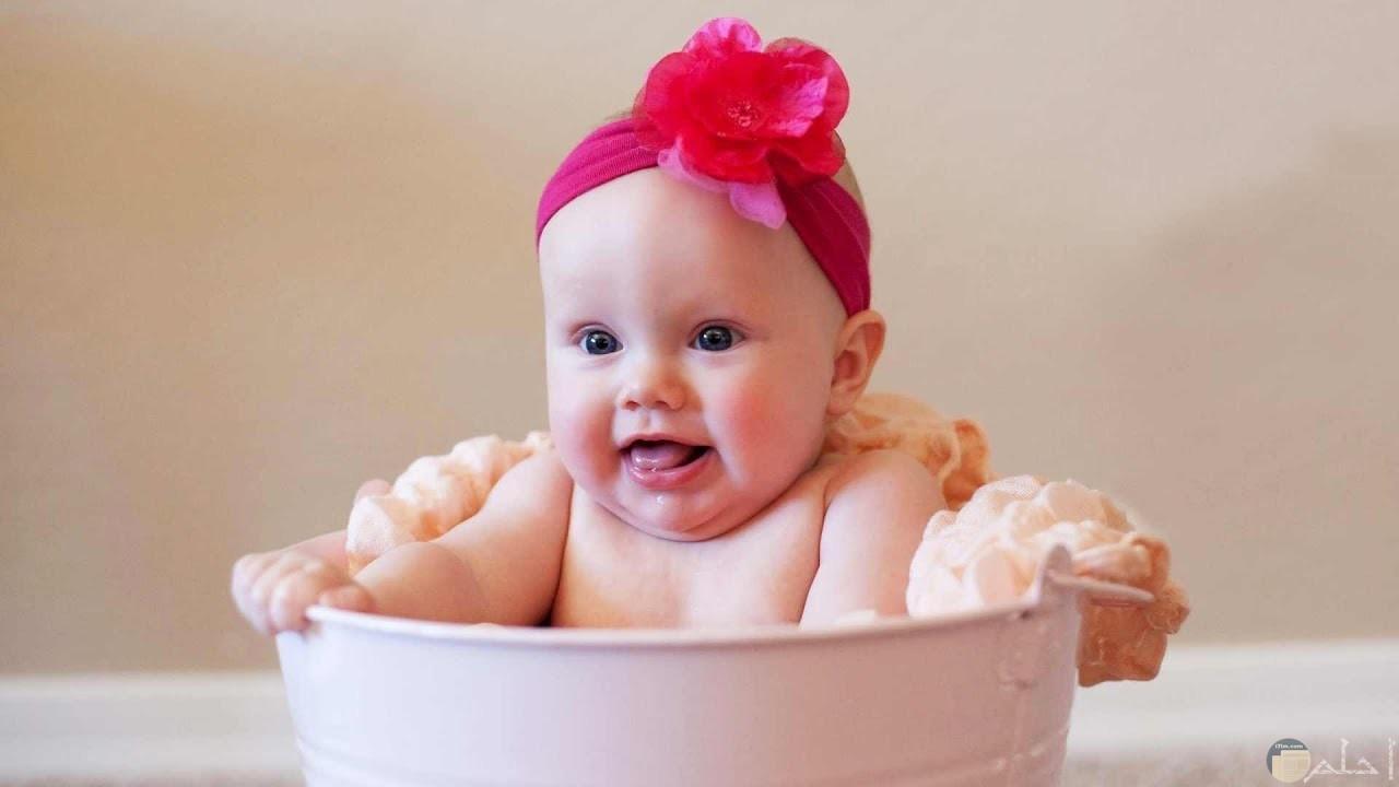 بنت صغيرة جميلة تجلس داخل إناء كبير.