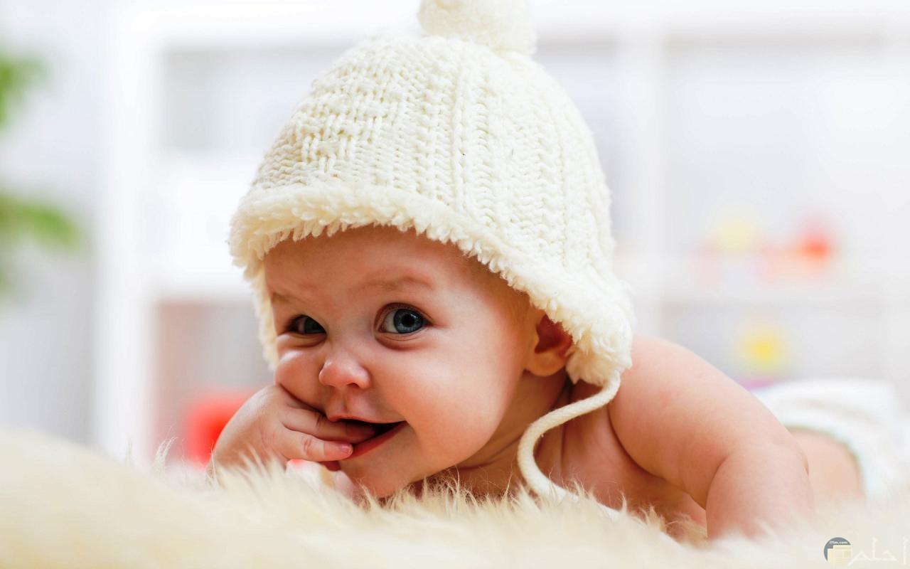 برائة الاطفال- طفل صغير بيضحك لابس طقية صوف بيضاء.