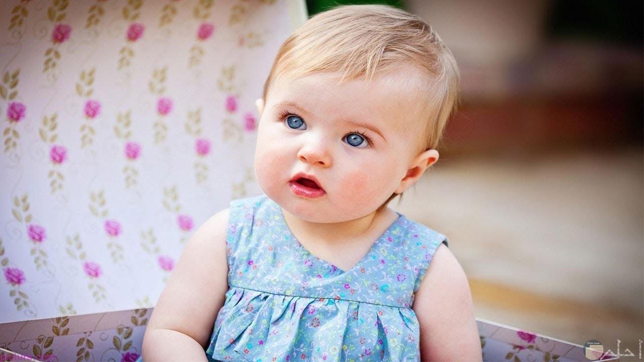 بنت صغيرة جميلة بفستان لبني.