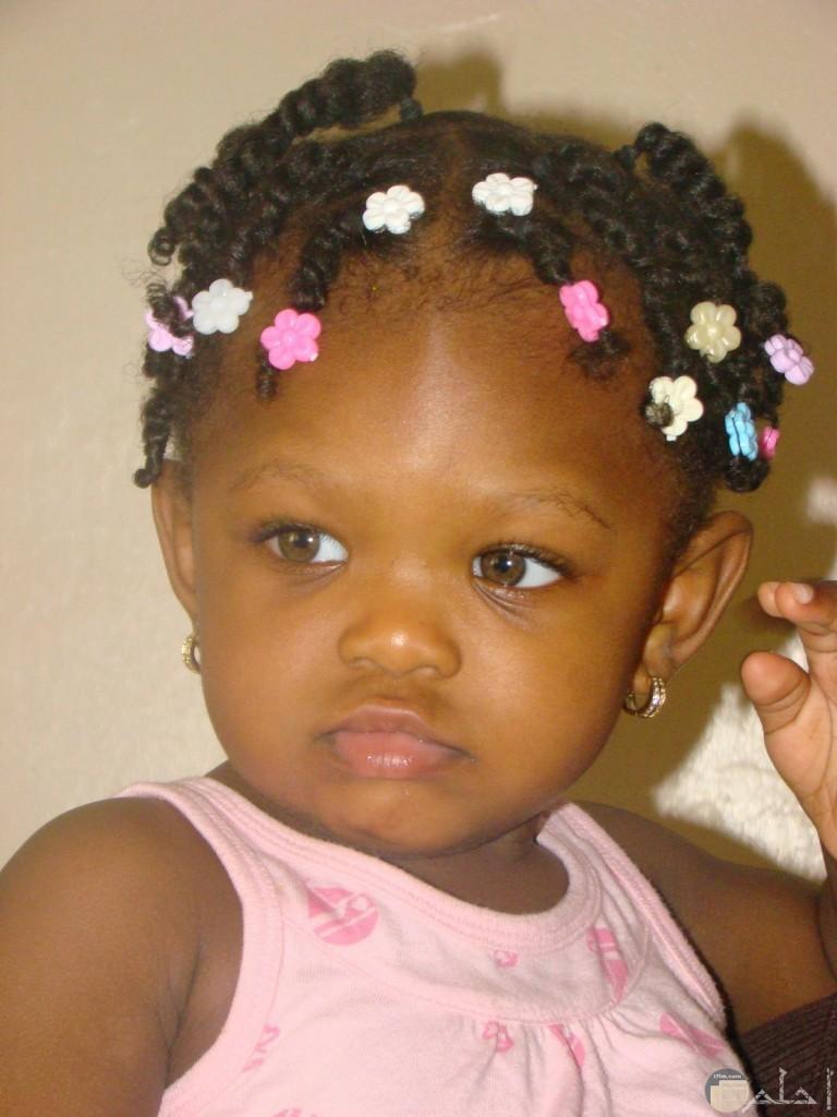 طفلة صغيرة سمراء و شعرها مضفر بشكل جميل.
