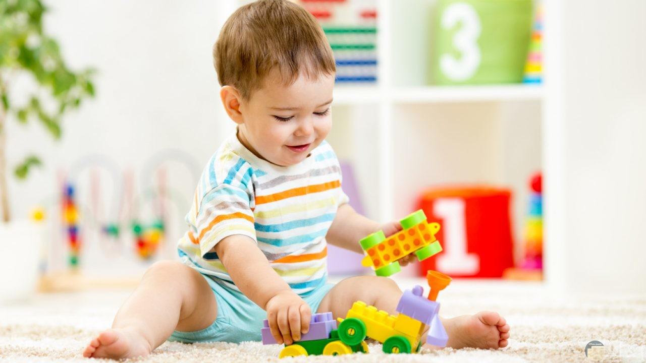 طفل صغير يلعب بالمكعبات.