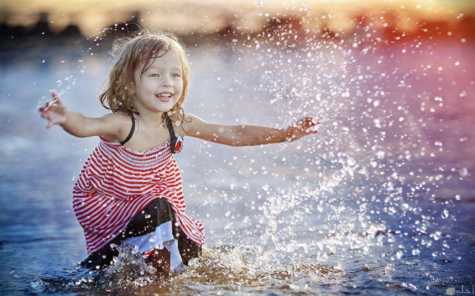 بنت صغيرة تلعب في الماء.