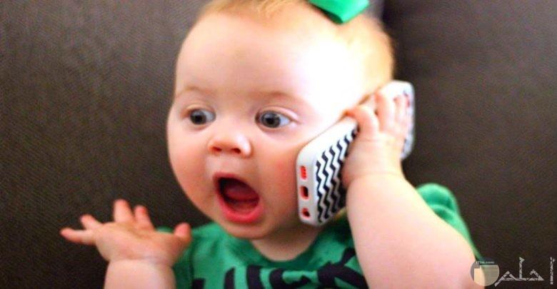 طفلة جميلة تمسك هاتف محمول و كأنها تتحدث بيه.