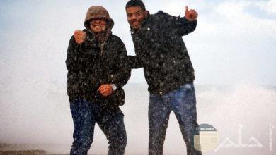 شبان مجنونان يقفان وسط العاصفة و يلتقطان صورة سوياً تحت الأمطار الغزيرة.