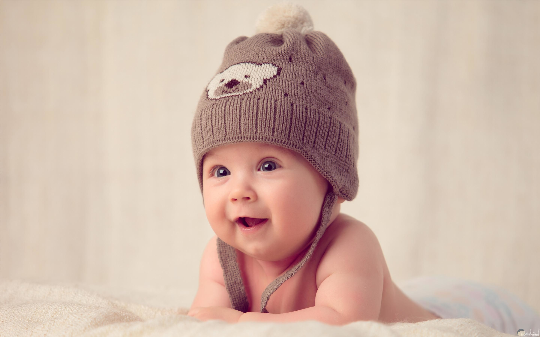 ولد صغير جميل و يرتدي طقية صوف على شكل دب.
