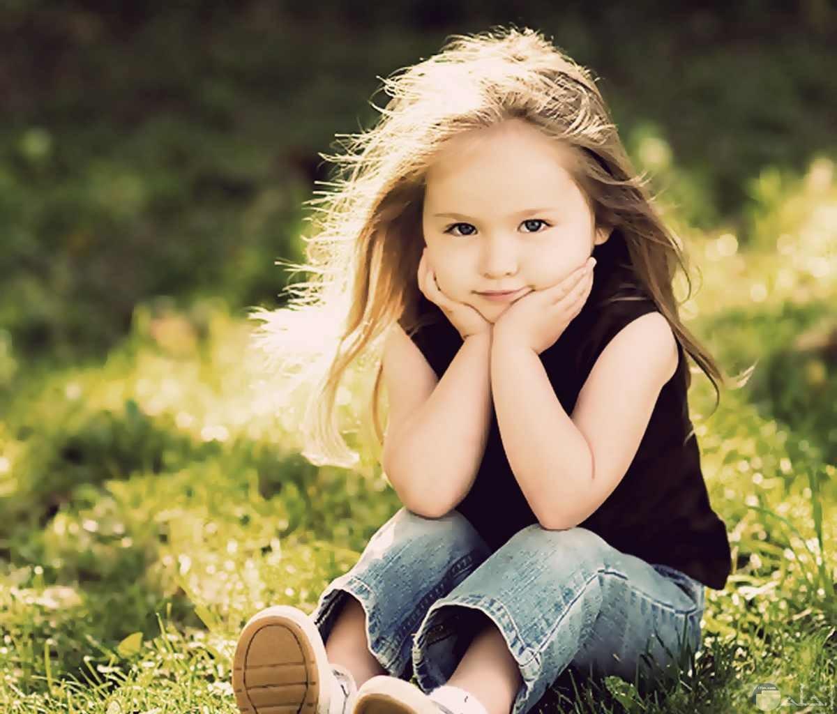 بنت صغيرة جميلة تجلس وسط العشب الأخضر.