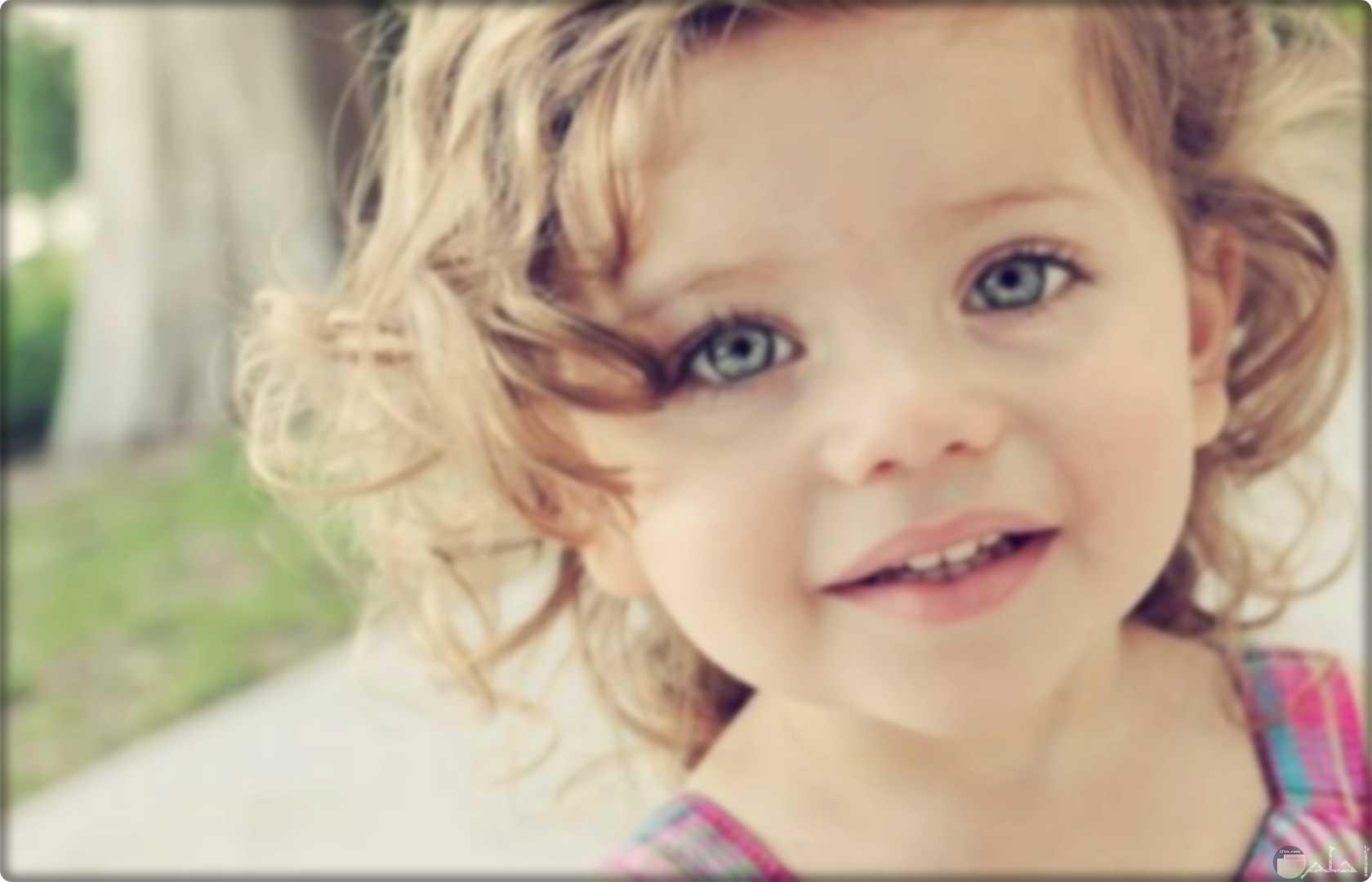 بنت صغيرة جميلة بشعر بنى مصفر و عين ملونة.