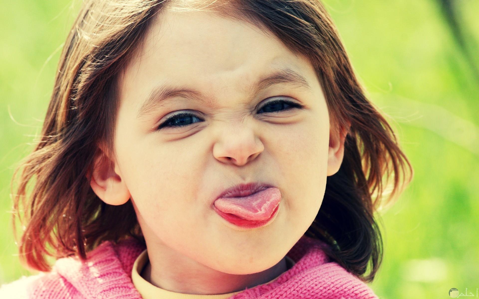 بنت صغيرة جميلة تخرج لسانها.