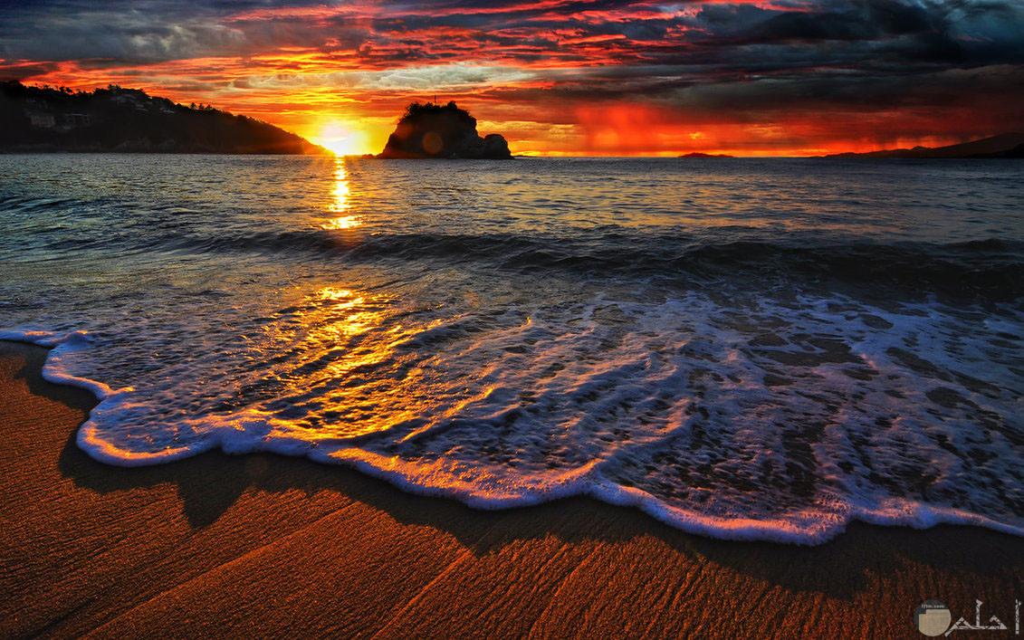 غروب الشمس بين صخرتين في البحر.