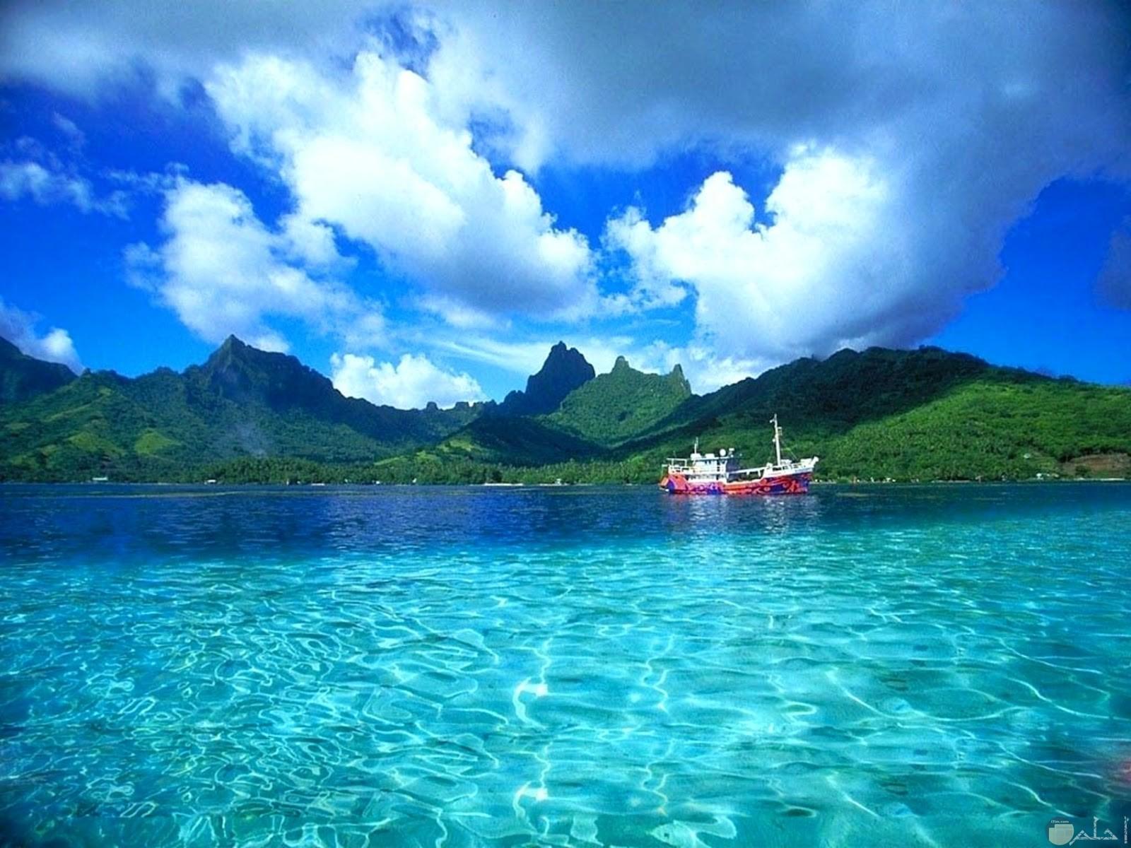 بحر له مياه صافية شفافة جميلة و جبال جزيرة تظهر من بعيد.
