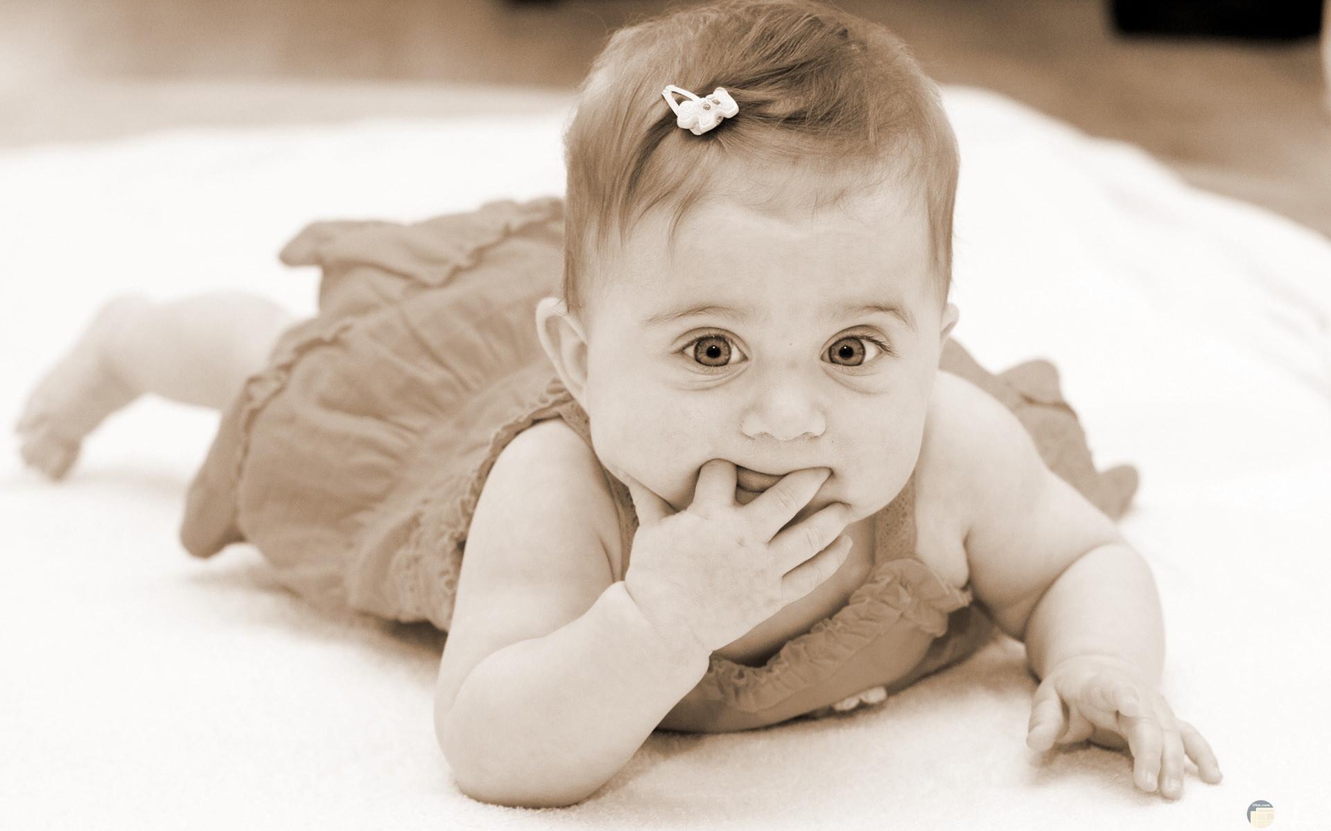 بنت صغيرة تضع فيونكة و أصابعها بفمها.