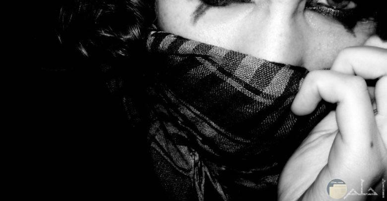 فتاة بعيون ساحرة دامعة تغطي نصف وجهها بوشاح كاروهات.