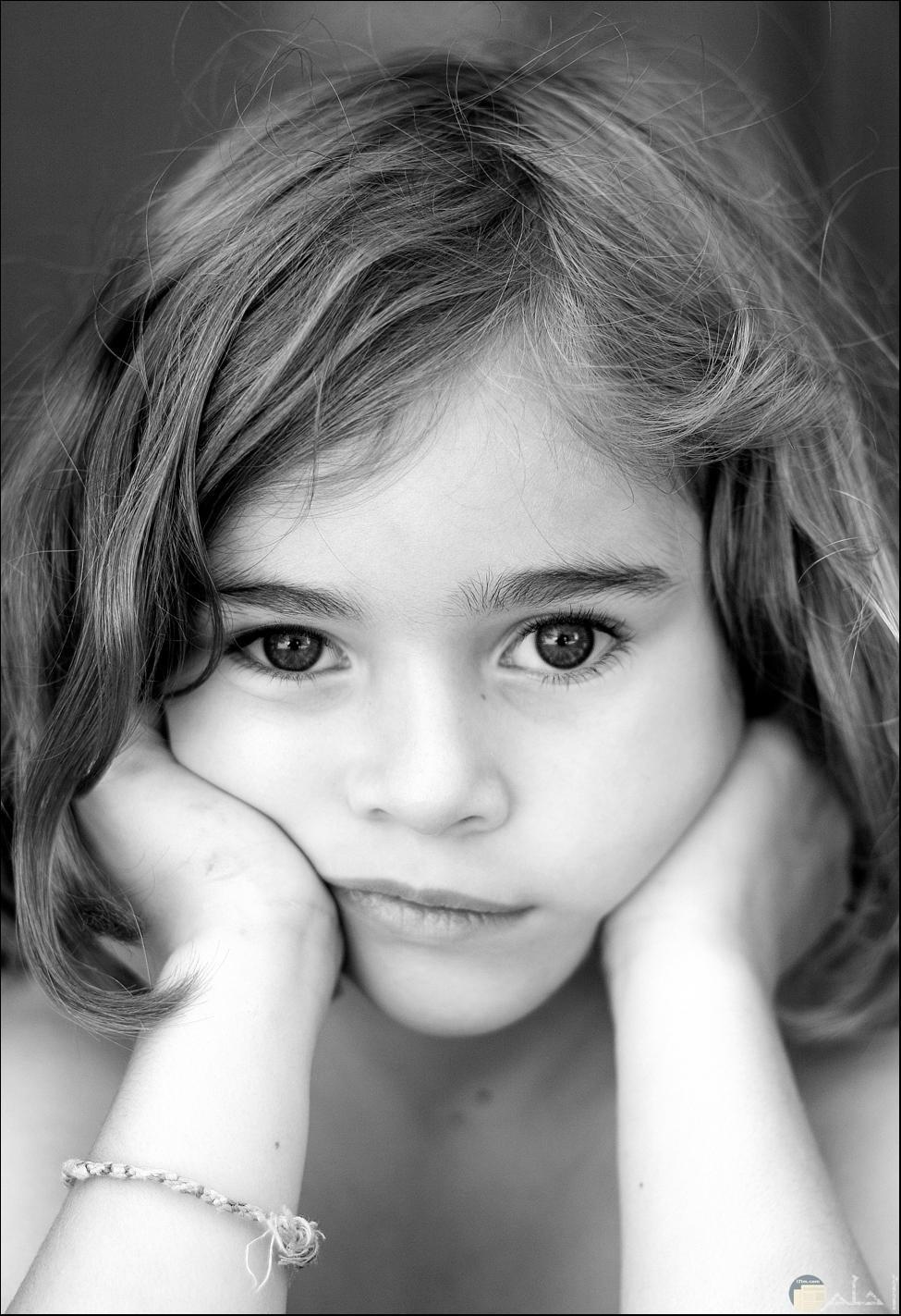 بنت صغيرة جميلة تضع يدها على خدها.
