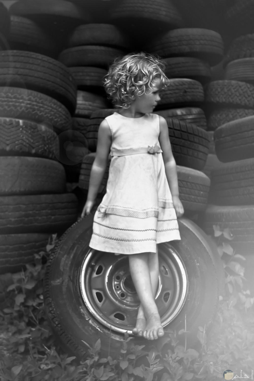 خلفية معبرة جميلة لفتاه صغيرة تجلس على عجل سيارة قديم.